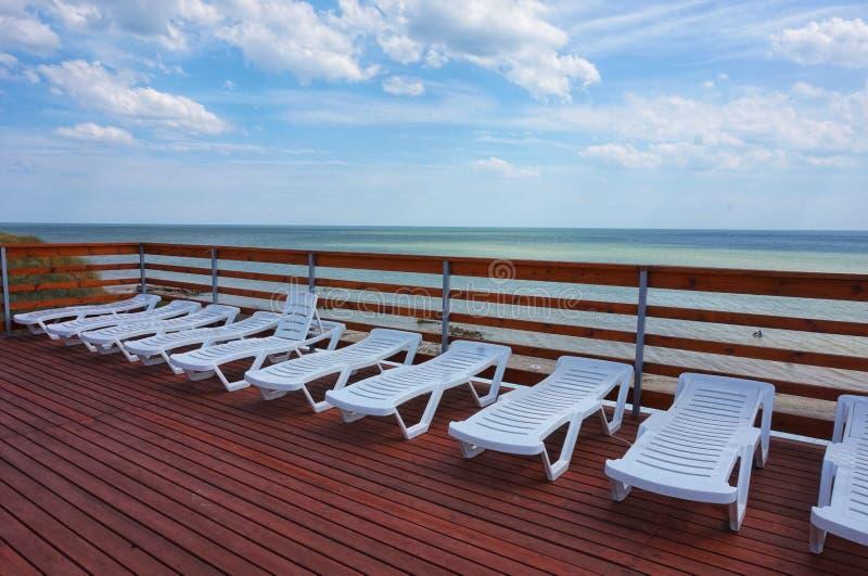 Plastic chaise zitkamerstribune dichtbij de pool royalty-vrije stock afbeeldingen
