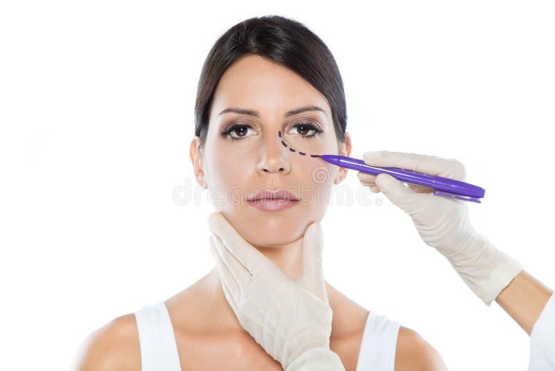Plastic chirurgentekening gestormde lijnen op haar geduldig gezicht van ` s royalty-vrije stock foto