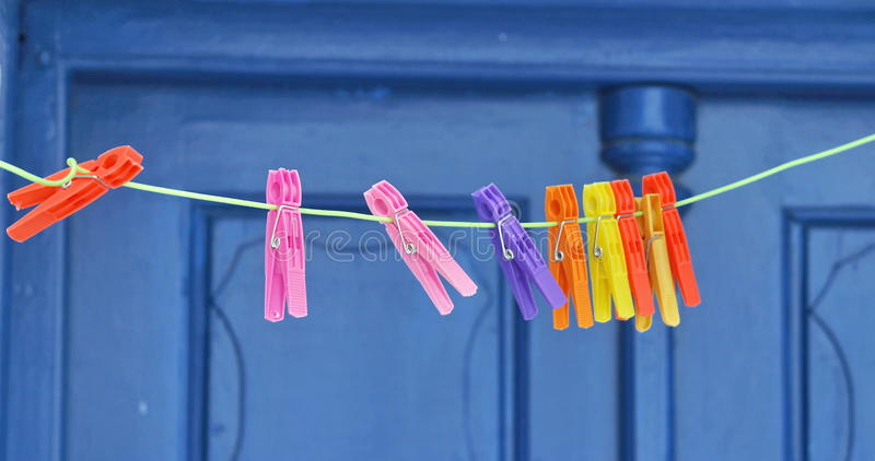 Plastic Clothes Pegs. Colored plastic clothes pegs on blue door background royalty free stock photography