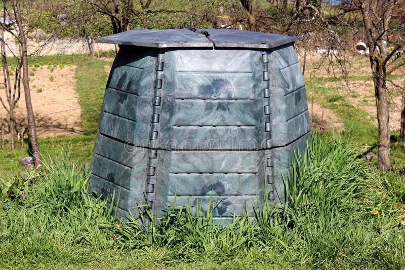 Plastic compost bin with dilapidated faded color surrounded with uncut grass and trees in local urban garden. On warm sunny spring day stock photos