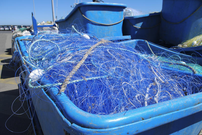 Plastic container with a fishing net. Blue plastic container with fishing net royalty free stock photo