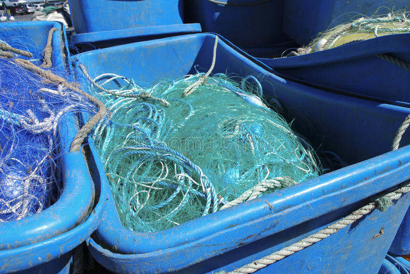 Plastic container with a fishing net. Blue plastic container with a green fishing net royalty free stock image