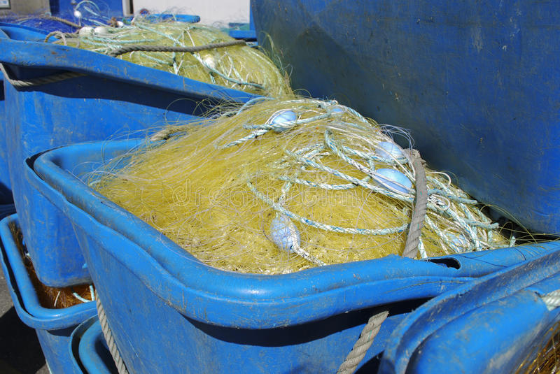 Plastic container with a fishing net. Blue plastic container with a yellow fishing net stock photography