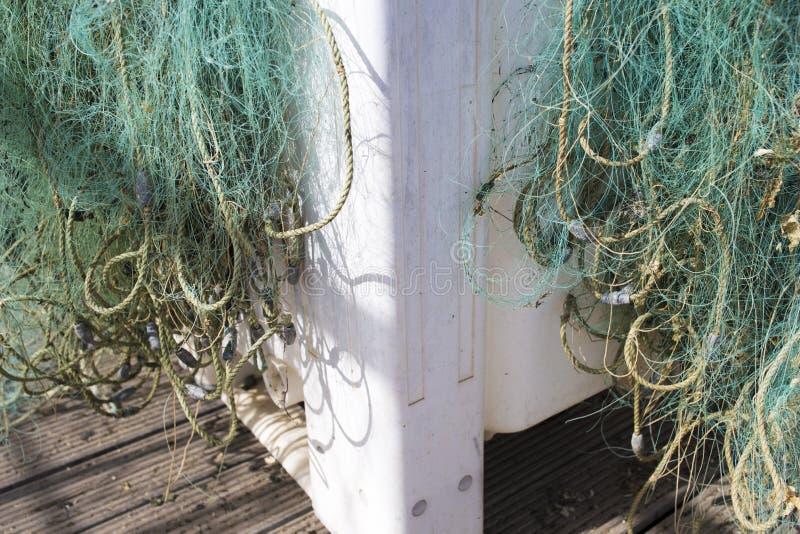 Plastic container full of green nylon fishing nets at fishing port stock photo