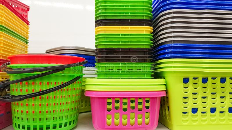 Plastic containers of different colors and prices are placed in a warehouse or store on display racks. Recycled plastic for sale, royalty free stock images