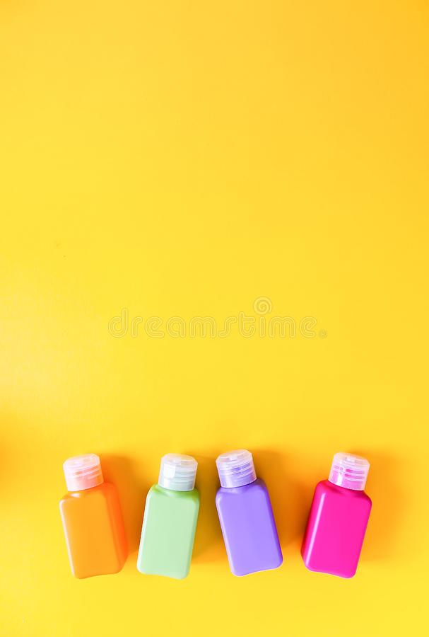 Plastic containers for different cosmetics storage purposes. Colorful bottles set on bright yellow background. royalty free stock photography