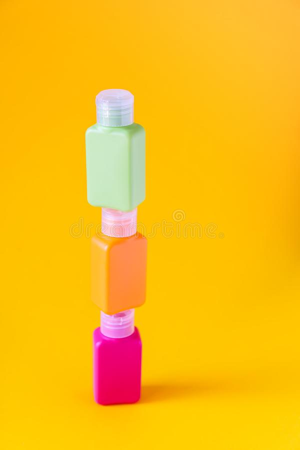 Plastic containers for different cosmetics storage purposes. Colorful bottles set on bright yellow background. stock image