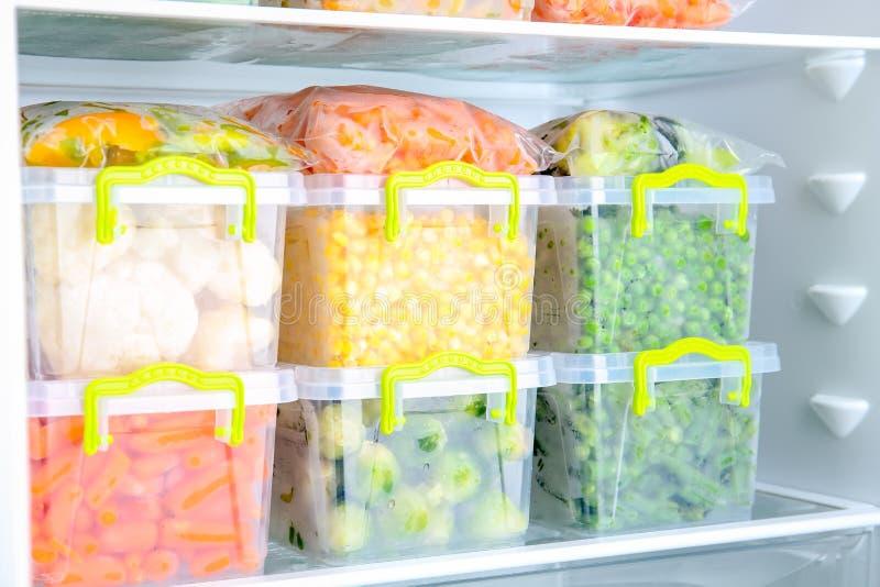 Plastic containers met diepgevroren groenten in ijskast stock foto