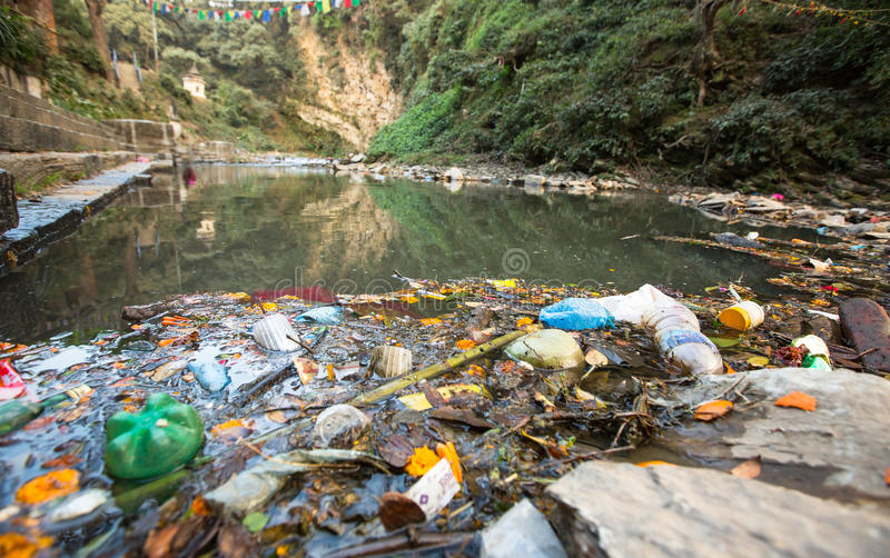 Plastic Contamination into Nature. Garbage and bottles floating on water. Environmental pollution in the Himalayas. Garbage in the water of river Bagmati stock images