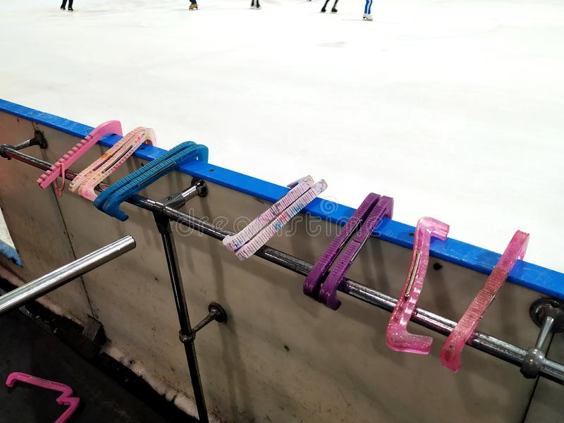 The plastic covers of different colors for skate blades. Several pieces lie on the bar of the ice rink. stock image