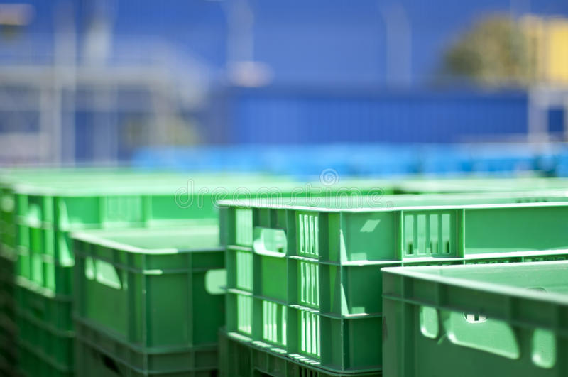 Plastic crates. Green plastic crates. Blurred blue background royalty free stock image