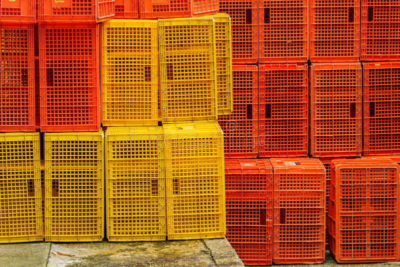 Plastic crates. Bright color of vegetable plastic crates pile horizontal on ground stock photos