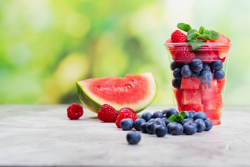 Plastic cup full of fresh cut fruits and berries. On summer green background. Healthy lifestyle concept. Copy space stock photo