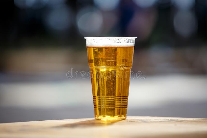 Plastic cup of light beer standing on the table royalty free stock photo