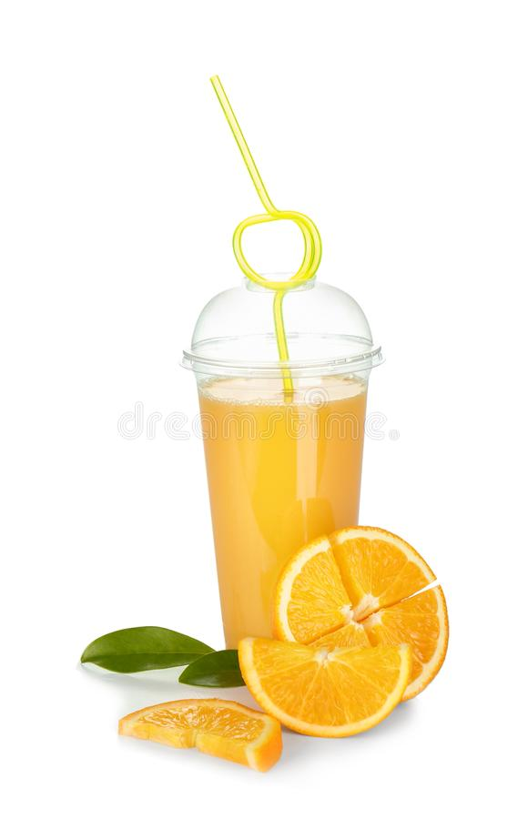 Plastic cup of orange juice and fresh fruit on white background royalty free stock photo