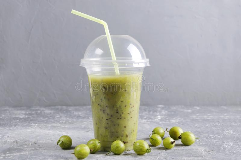 Plastic cup of refreshing smoothie.Gooseberry blended beverage royalty free stock photography