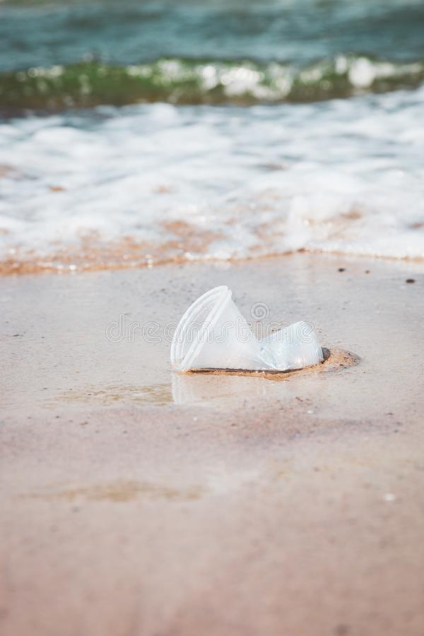 Plastic cups littering sea water at ocean beach stock photography