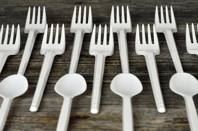 Plastic cutlery. Disposable plastic forks and spoons on wooden background royalty free stock photos