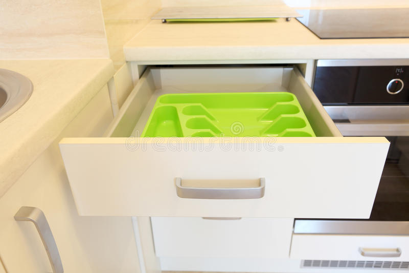 Plastic cutlery tray in kitchen drawer. Empty green plastic cutlery tray in kitchen drawer stock image