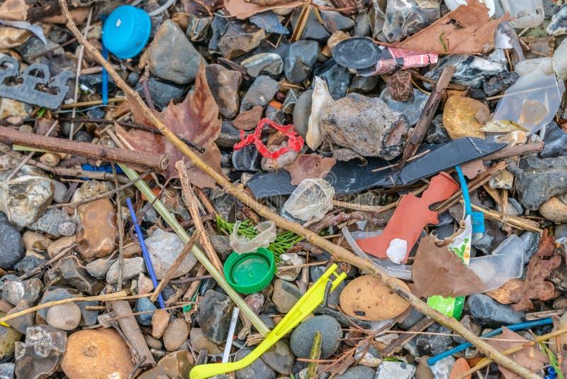 Plastic die verontreiniging op het strand wordt gevonden De accumulatie van plastic voorwerpen in het milieu van de Aarde be?nvlo stock afbeelding