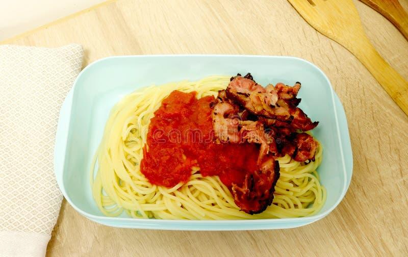 Plastic die voedselcontainer met spaghetti, tomatensaus en bacon wordt ingepakt royalty-vrije stock afbeeldingen