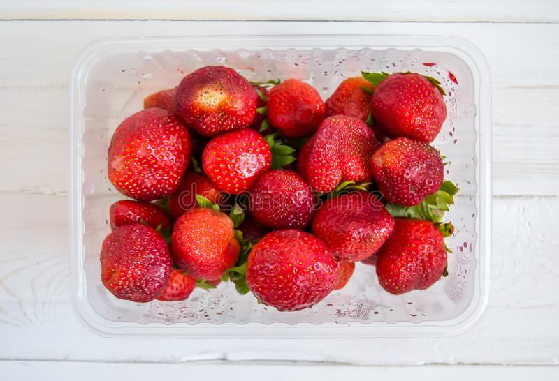 Plastic dienblad met rode aardbeien op een witte houten hoogste mening als achtergrond royalty-vrije stock fotografie