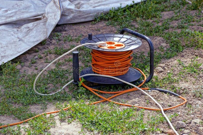 Plastic drager met rozetten en oranje kabel op groen gras royalty-vrije stock foto's