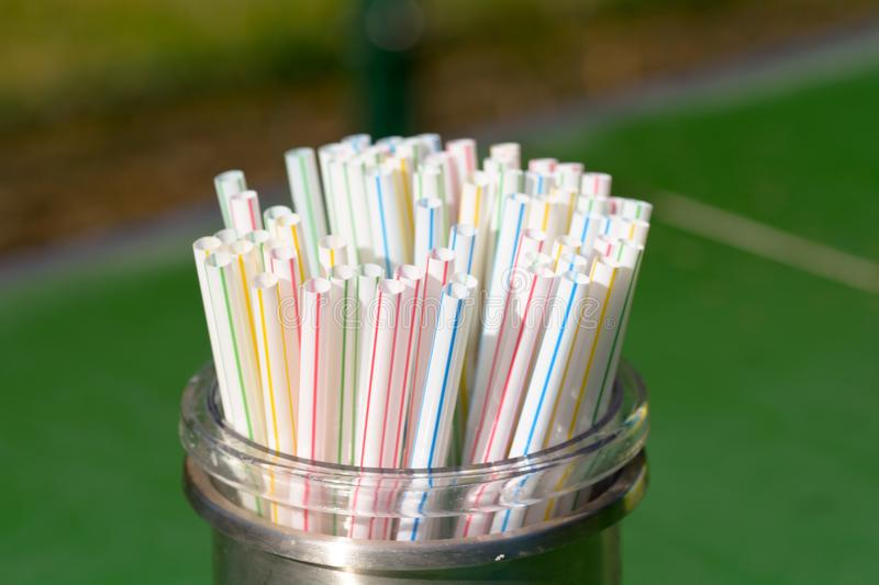 Plastic drinks straws in container in cafe. Plastic drinks straws in container on table in cafe royalty free stock photography