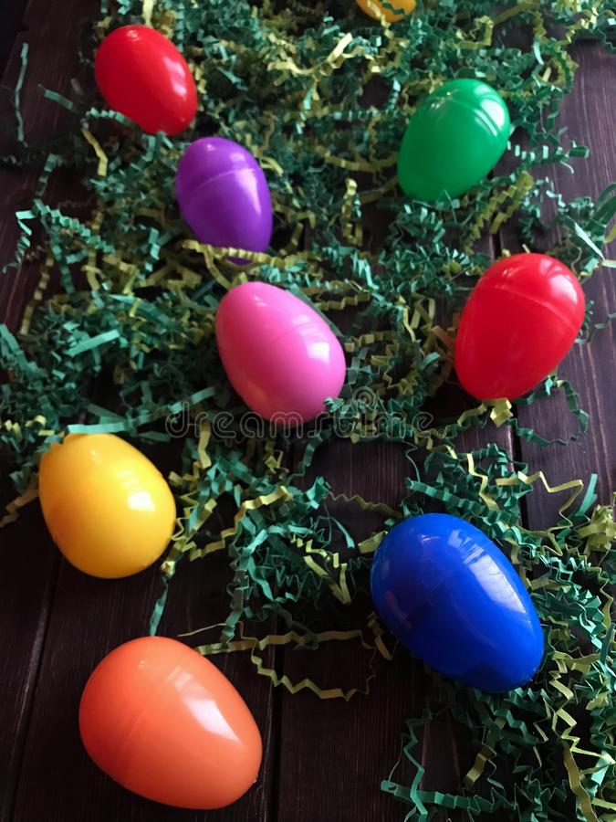 Group Of Plastic Easter Eggs On Paper Grass And A Wooden Background