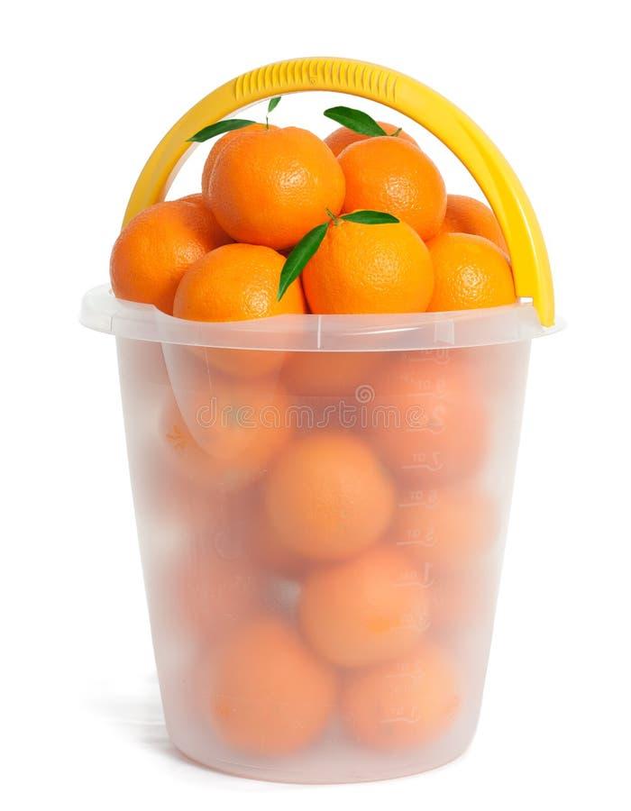 Plastic Emmer met oranje vruchten stock afbeeldingen