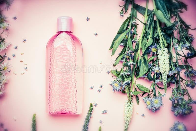 Plastic fles met tonisch of micellar reinigend water met verse kruiden en bloemen op roze achtergrond, hoogste mening royalty-vrije stock fotografie