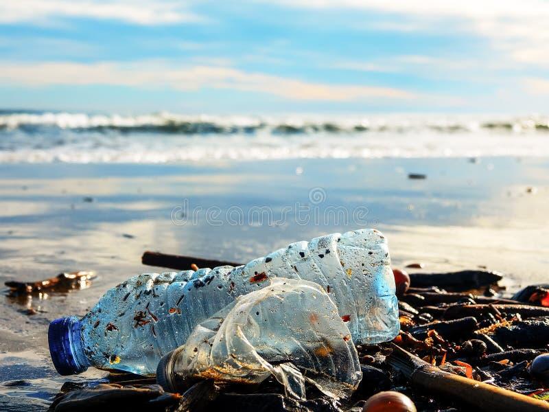 Plastic fles op nat die zand door de overzeese golf wordt weggegooid royalty-vrije stock afbeelding