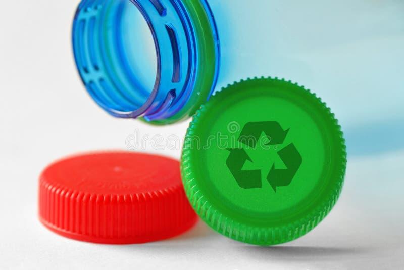 Plastic flesje en doppen met recyclesymbool op witte achtergrond - Concept van recyclebare voorwerpen en materialen stock foto