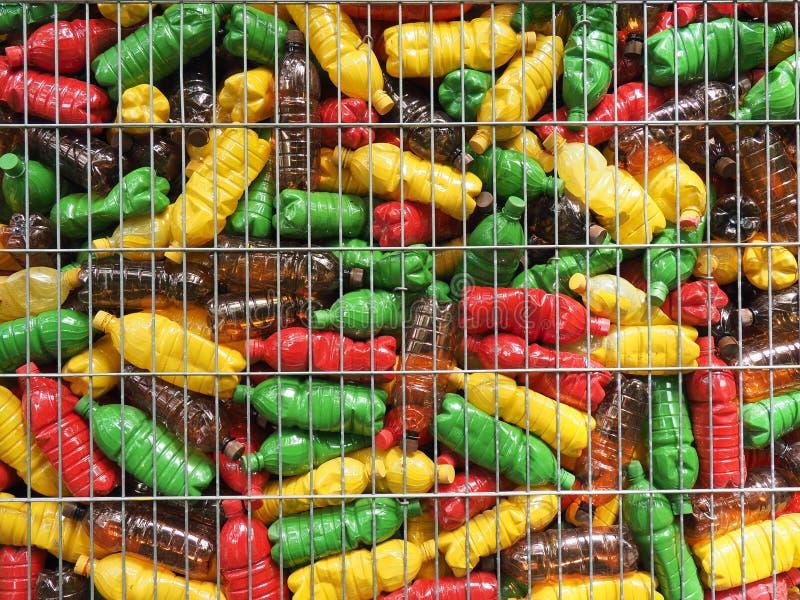 Plastic flessen achter de tralies stock afbeelding