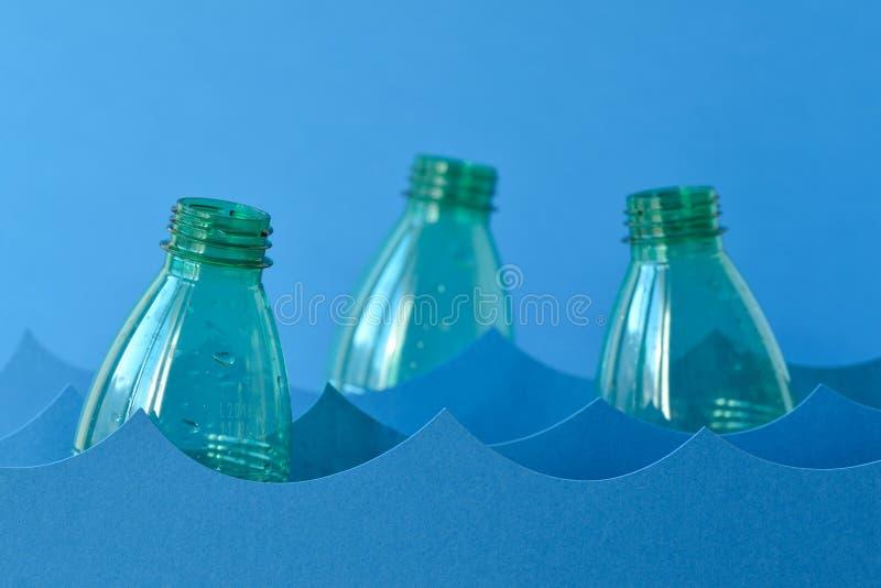 Plastic flessen die op water drijven - Overzees verontreinigingsconcept stock afbeeldingen