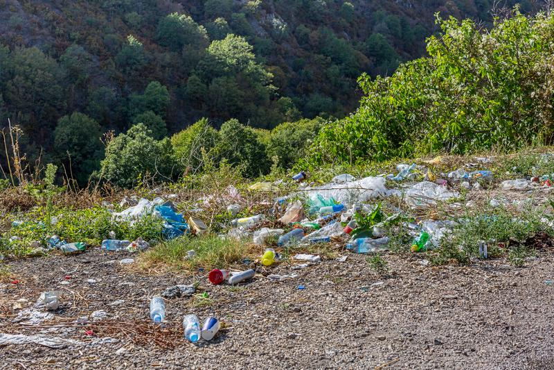 Plastic flessen en ander afval langs de bergweg Heel wat afval bij kant van de weg Concept milieuvervuiling royalty-vrije stock afbeeldingen