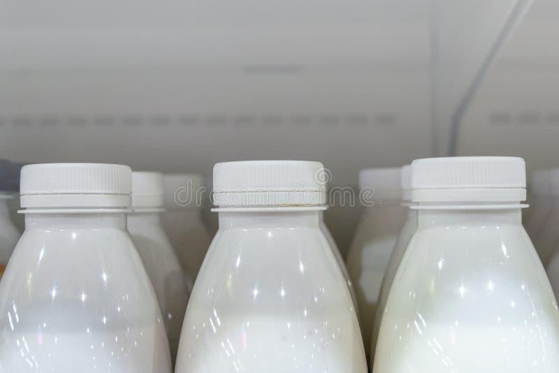 Plastic flessen met melk op de plank in de opslag Witte achtergrond De ruimte van het exemplaar stock afbeeldingen