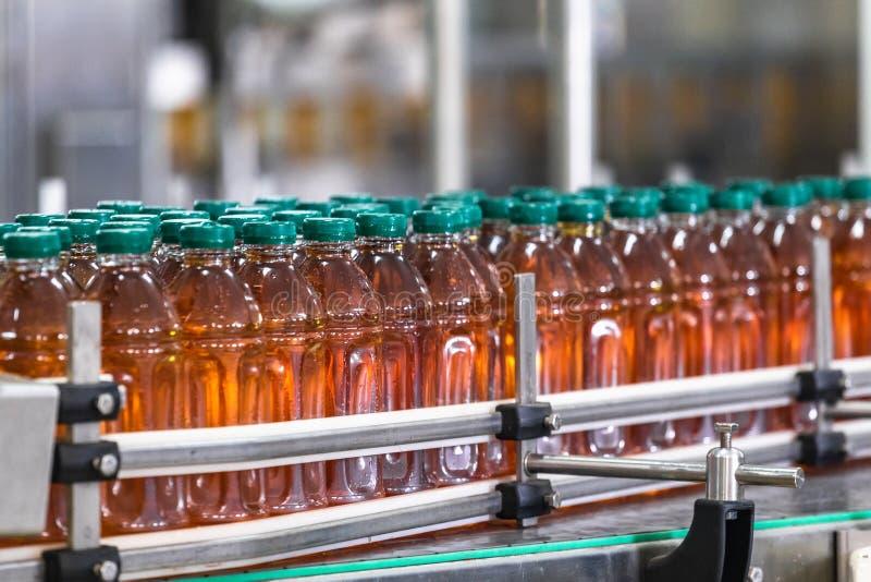 Plastic flessen met vers organisch binnen sap op automatische transportband of lijn in van de drankfabriek of installatie binnenl stock foto