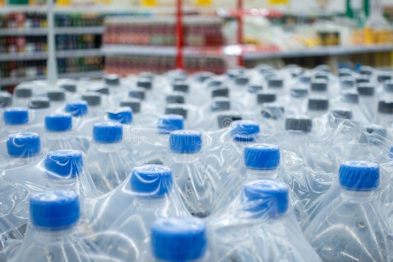 Plastic flessen in pakken Waterflessen - plastic van de het pakhuisopslag van de flessenfabriek het voedselachtergrond royalty-vrije stock foto's