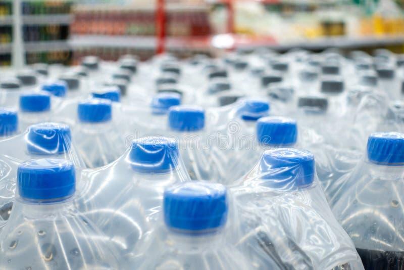 Plastic flessen in pakken Waterflessen - plastic van de het pakhuisopslag van de flessenfabriek het voedselachtergrond stock foto's