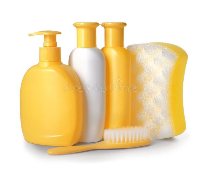 Plastic flessen van babycosmetischee producten, douchespons en borstel op witte achtergrond stock foto's