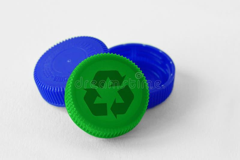 Plastic flessendoppen met recyclesymbool op witte achtergrond - Concept van recycleerbare voorwerpen en materialen royalty-vrije stock afbeelding