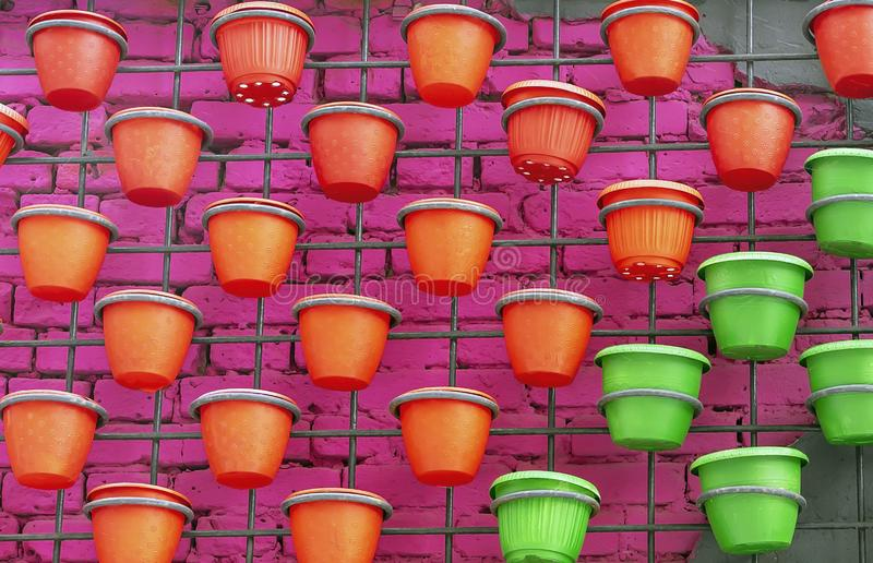 Plastic flower pots on a brick wall background stock image