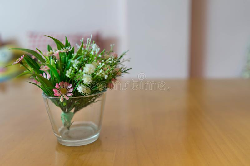 plastic flowers in vase on wooden table and blur pink wall background in resterant,selective focus stock photography