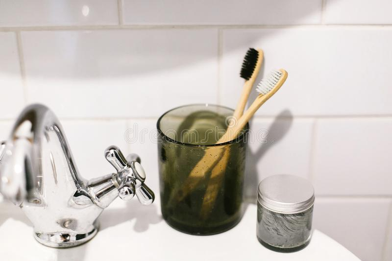Plastic free bathroom items. Eco natural bamboo toothbrushes in glass and organic charcoal toothpaste in glass jar on sink in royalty free stock photo
