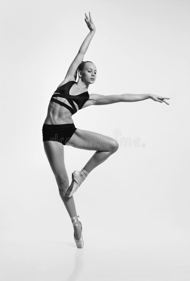 Plastic girl in pointe shoes b&w. A plastic girl in pointes and black lingerie makes a graceful pose royalty free stock photo