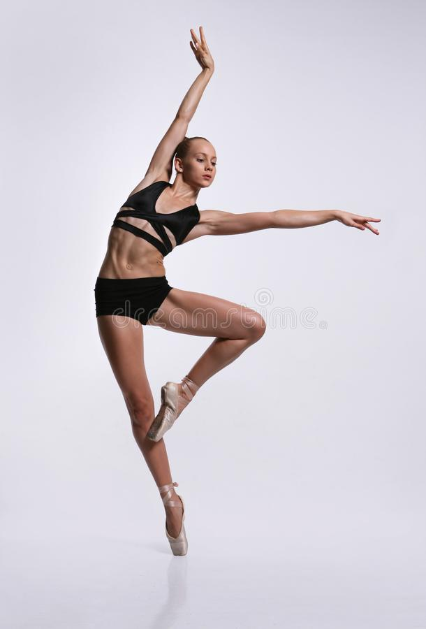 Plastic girl in pointe shoes. A plastic girl in pointes and black lingerie makes a graceful pose royalty free stock photos