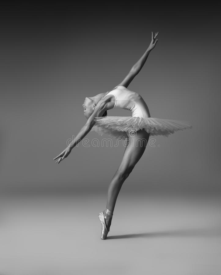 Plastic girl in pointe shoes b. A plastic girl in pointes and tutu makes a graceful pose royalty free stock images