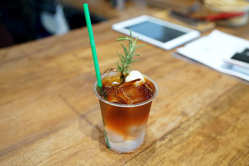 A plastic glass of Iced americano coffee mixed with craft soda and lychee juice and topped with rosemary leaves and fresh lychee royalty free stock image