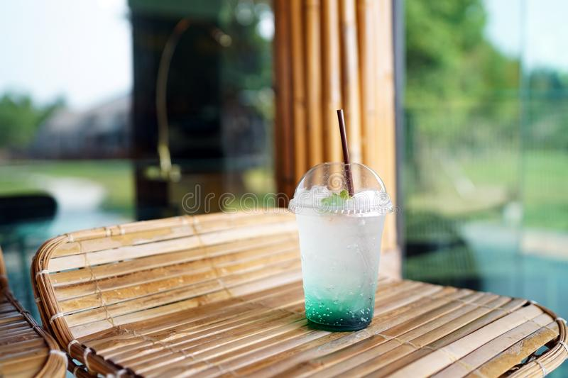 A plastic glass of Iced mojito soda with mint on blurred background. royalty free stock photography